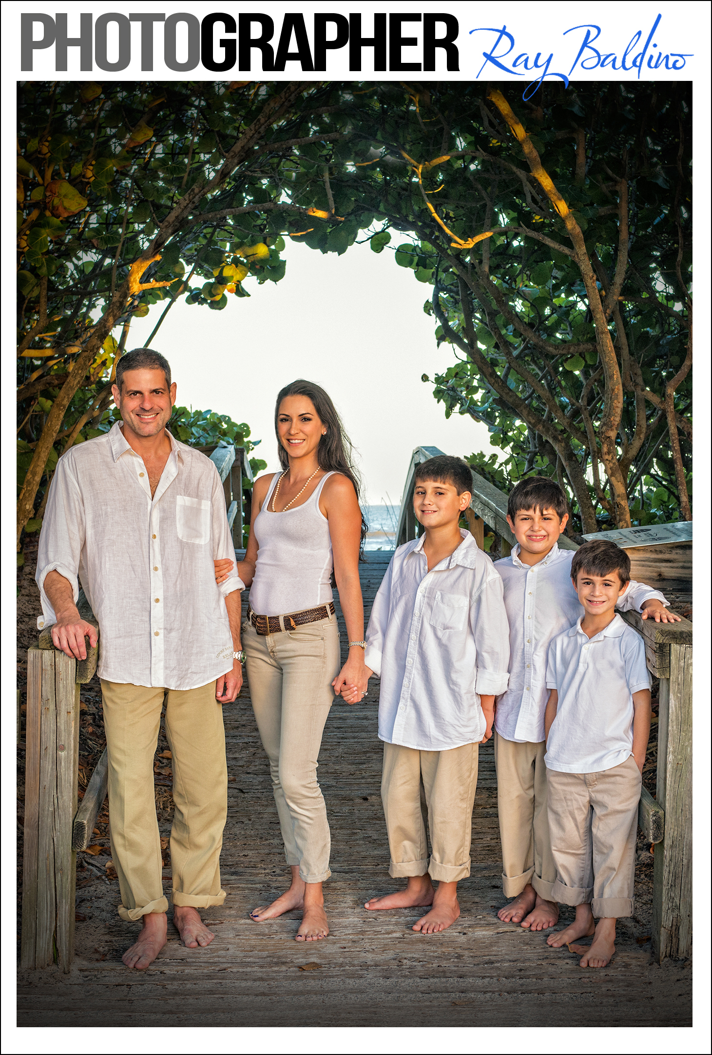 family-beach-photography-by-ray-baldino-in-cocoa-beach-florida-this-image-is-a-picture-of-a-family-with-their-children-standing-in-front-of-the-entrance-to-the-beach